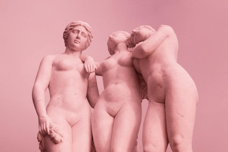 A pink photograph of three statues of nude women posed together like close friends.