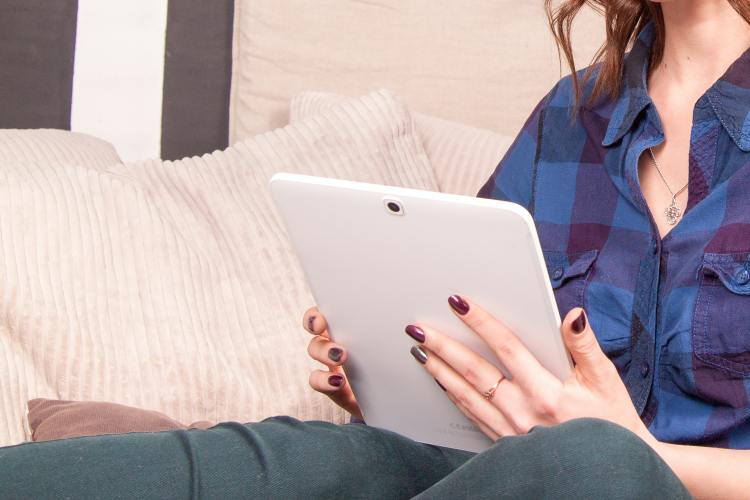 Woman in a blue check flannel holds a white tablet.